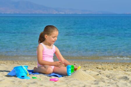 kyklades: Real adorable toddler girl playing with her toys at the beach Stock Photo
