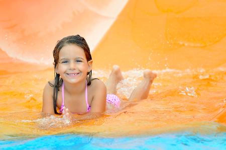 Adorable toddler girl on water slide at aquapark. Summer vacation