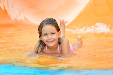 summer vacation bikini: Adorable toddler girl on water slide at aquapark. Summer vacation