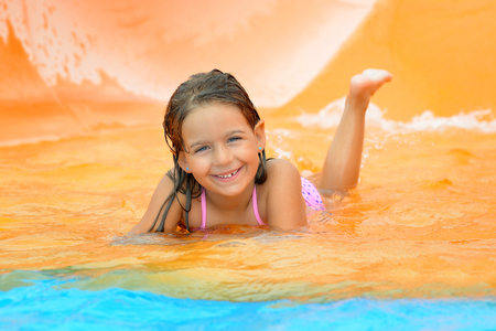 child play: Adorable toddler girl on water slide at aquapark. Summer vacation