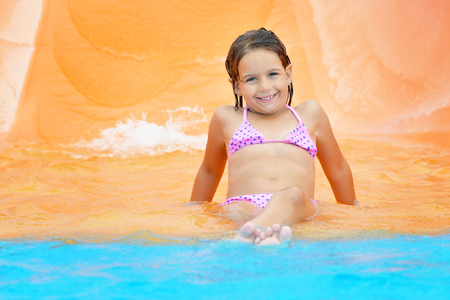 wet suit: Adorable toddler girl on water slide at aquapark. Summer vacation