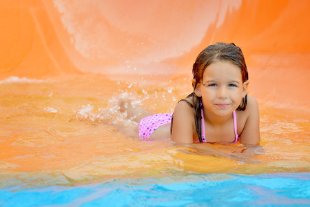 summer holiday bikini: Adorable toddler girl on water slide at aquapark. Summer vacation