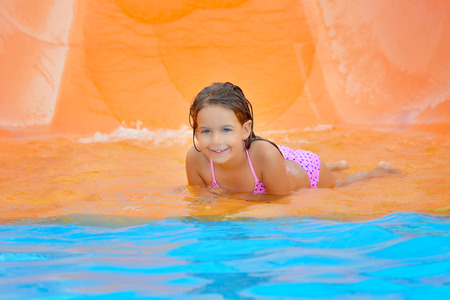 pool water: Adorable toddler girl on water slide at aquapark. Summer vacation
