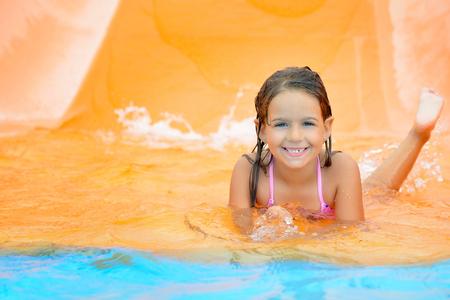 smiling child: Real toddler girl enjoying her summer vacation on water slide at aquapark