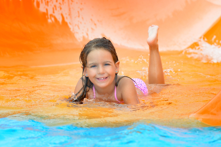 child bikini: Real toddler girl enjoying her summer vacation on water slide at aquapark