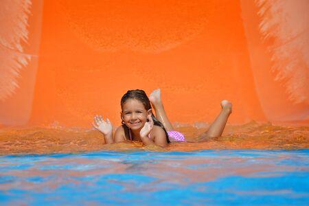 summer vacation bikini: Real toddler girl enjoying her summer vacation on water slide at aquapark