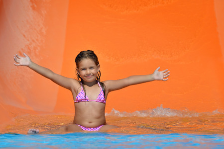 little child: Real toddler girl enjoying her summer vacation on water slide at aquapark