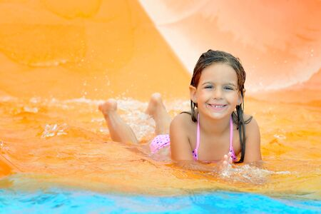 little child: Adorable toddler girl on water slide at aquapark. Summer vacation