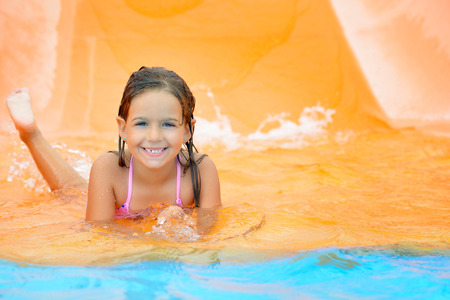 baby swimming: Real toddler girl enjoying her summer vacation water slide at aquapark Stock Photo