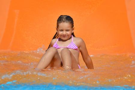 water activity: Adorable toddler girl on water slide at aquapark. Summer vacation