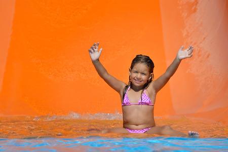 niños nadando: la muchacha del niño real que disfruta de sus vacaciones de verano en tobogán en el parque acuático