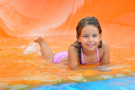 summer holiday bikini: Real toddler girl enjoying her summer vacation on water slide at aquapark