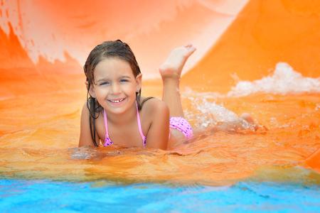 child play: Real toddler girl enjoying her summer vacation on water slide at aquapark