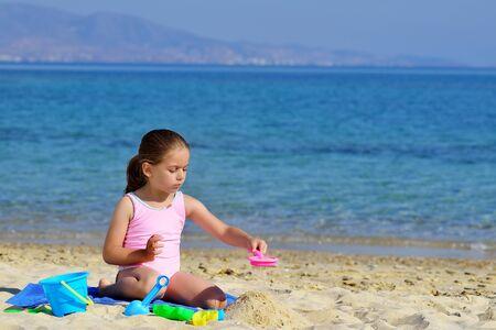kyklades: Real toddler girl enjoying her summer vacation at beach
