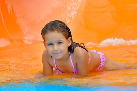 Real adorable toddler girl enjoying her summer vacation on waterslide at aquapark Stock Photo
