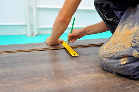parquet floor layer: Worker carpenter doing laminate floor work Stock Photo