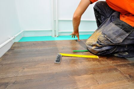 Worker carpenter doing laminate floor work Stock Photo