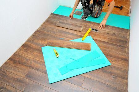 parquet floor layer: Worker carpenter doing laminate floor work Stock Photo