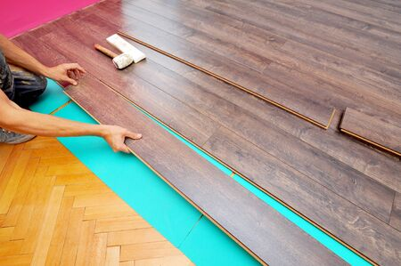 Worker carpenter doing laminate floor work Reklamní fotografie