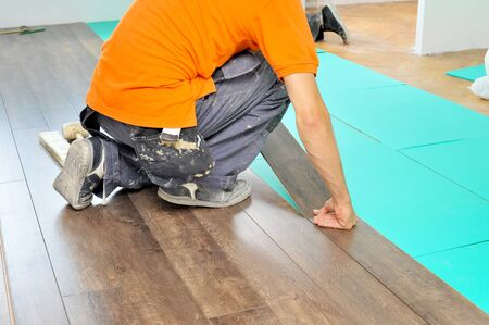 parquet floor layer: Real carpenter doing laminate floor work Stock Photo