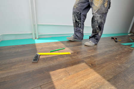Real carpenter doing laminate floor work Stock Photo