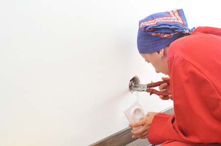 Real woman electrician fixing socket electricity problem