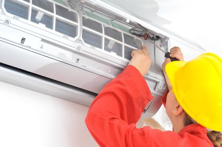 Real young woman electrician adjusting air conditioner system Stock Photo
