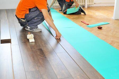 parquet floor layer: Real carpenter doing laminate floor work Stock Photo