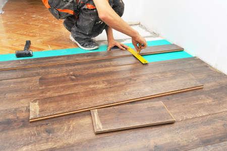 padding: Worker carpenter doing laminate floor work Stock Photo