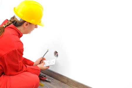 fixing: Woman electrician fixing socket Stock Photo