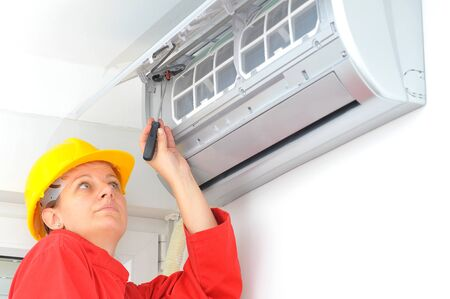 erector: Real young woman worker adjusting air conditioner system
