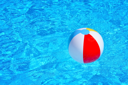 furlough: Colorful inflatable ball floating in swimming pool, summer vacation concept