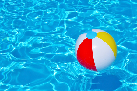 the furlough: Colorful inflatable ball floating in swimming pool, summer vacation concept