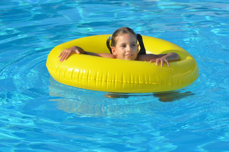 dominican: Adorable toddler relaxing in swimming pool, summer vacation concept