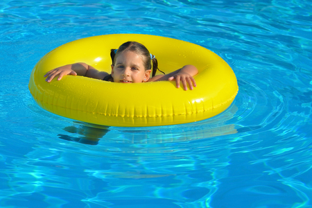 Adorable toddler relaxing in swimming pool, summer vacation concept