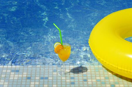 the furlough: Cocktail and colorful tube next to swimming pool, summer vacation concept Stock Photo