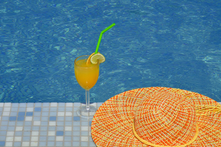 Cocktail and colorful hat next to swimming pool, summer vacation concept Stock Photo