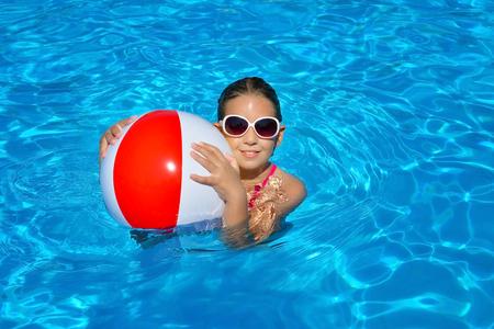 Chica adorable real relajante en la piscina, concepto de vacaciones de verano