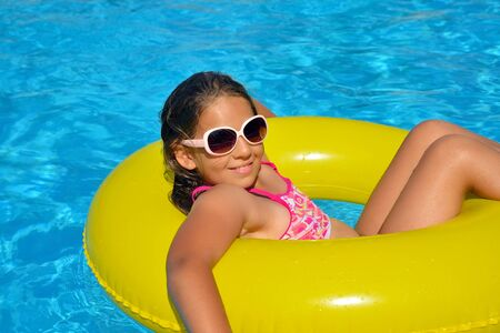 Real adorable girl relaxing in swimming pool, summer vacation concept Stockfoto