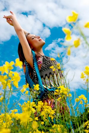 Young happy girl in yellow flowers, outdoor photo session photo