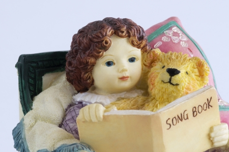 Ceramic doll with a bear reading a book photo