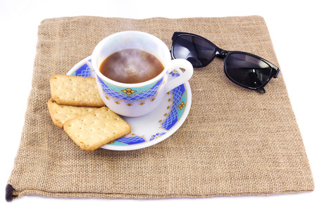 Cup of coffee  with cookies and sunglasses with white background, horizontal top view
