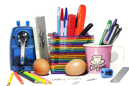 engrapadora: Stationery background - Group of stationery tools - sharpener, color pencils, notebooks, pens, stapler , cutter . coffee , eggs on white background Foto de archivo