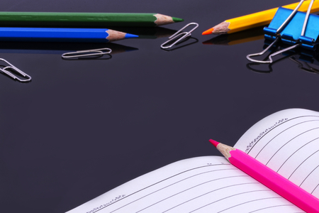 Paper clips , Color pencil and Notebook  on black background