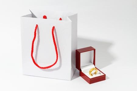 white paper bag: Bolsa de papel blanco y el anillo de oro de hombre, fondo blanco