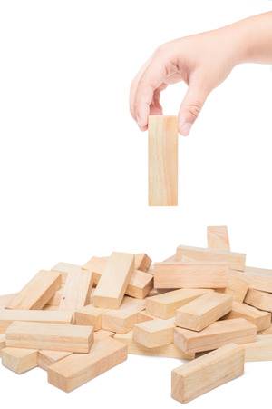 building bricks: Hand playing with the wood game (jenga). on white background. Stock Photo