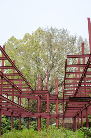steelwork: a big tree behind structural steel buildings the unfinished