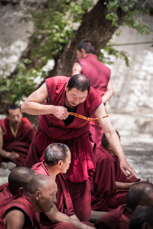 reside: LHASA, TIBET - MAY 2016 - A senior monk expresses his thought to his fellow monks in a debate at Sera monastery, Lhasa, Tibet. The debate happens daily in the monastery courtyard. It is open to the public.