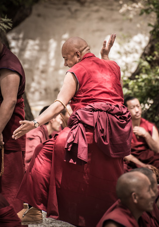 reside: LHASA, TIBET - MAY 2016 - A senior monk challenges his fellow monks to debate in Sera monastery, Lhasa, Tibet. The debate happens daily in the monastery courtyard. It is open to the public.