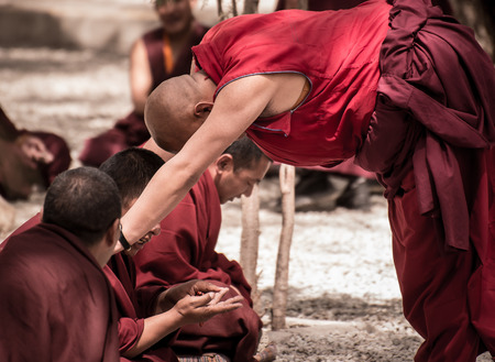 reside: LHASA, TIBET - MAY 2016 - A senior monk listens to his fellow monks argument in a debate at Sera monastery, Lhasa, Tibet. The debate happens in the monastery courtyard. It is open to the public.